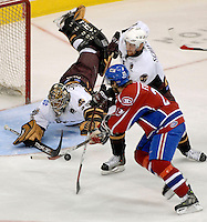 The Hershey Bears goalie Frederic Cassivi, left,  stops a shot by Hamilton Bulldogs right winger Jonathan Ferland (21) as Bears defenseman Jeff Schultz, center,  atempts  a check in the first period of game one in the AHL Calder Cup playoffs Friday, June 1, 2007 in Hershey, Pa. (AP Photo/Bradley C Bower)