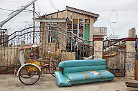 Philippines. Province Eastern Samar. Guiuan. Daily family's life. A woman dries laundry on a rope in the living room. A blue couch and a tricycle on the street's pavement. The 300 kph (or km/h) winds of typhoon Haiyan has blown and destroyed houses, ripped rooftops apart and smashed walls. The town of Guiuan was the first to face the fury of typhoon Haiyan when it barrelled into the Philippines on november 8 2013. Typhoon Haiyan, known as Typhoon Yolanda in the Philippines, was an exceptionally powerful tropical cyclone that devastated the country. Haiyan is also the strongest storm recorded at landfall in terms of wind speed (300 km per hour). 28.11.13 © 2013 Didier Ruef
