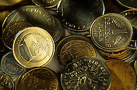 One euro coin among a pile of franc and deutsche mark coins.