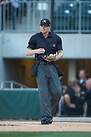 Home plate umpire Richard Riley gets some new baseballs between innings of the International League game between the Scranton/Wilkes-Barre RailRiders and the Charlotte Knights at BB&T BallPark on April 12, 2018 in Charlotte, North Carolina.  The RailRiders defeated the Knights 11-1.  (Brian Westerholt/Four Seam Images)
