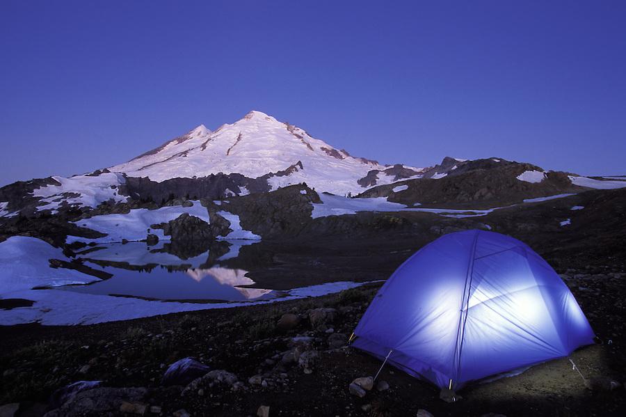 Tent glowing below Mt Baker on a clear evening, North Cascades, Cascade Mountains, Washington