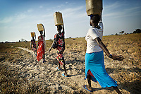 Women carrying water from a hand pump in the village to their homes in South Sudan.
