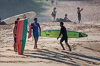 A surfer on the beach holds a broken surfboard, Waimea Bay, North Shore, O'ahu.