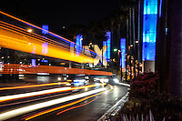 Balanced on a curb at night shooting the famous LAX sign with light streaks from passing vehicles.