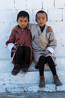 Punakha, Bhutan.  Two Young Boys Wearing Traditional Gho, with Cell Phones, Chimi Village.