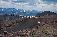 View from top of Mt Evans, yellow sportscar is climbling up the road to the top. Mt Evans Road is the highest paved road in the USA