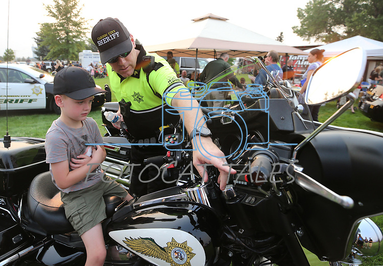Carson City Sheriff's Sgt. Earl Mays shows Chayson Schierholt, 5, his motor unit during the 16th annual National Night Out event, hosted by the Carson City Sheriff's Office, in Carson City, Nev., on Tuesday, Aug. 7, 2018.<br />Photo by Cathleen Allison/Nevada Momentum