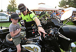Carson City Sheriff's Sgt. Earl Mays shows Chayson Schierholt, 5, his motor unit during the 16th annual National Night Out event, hosted by the Carson City Sheriff's Office, in Carson City, Nev., on Tuesday, Aug. 7, 2018.<br />
