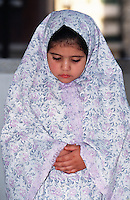 Portrait of a young Muslim girl in traditional attire praying. Egypt.
