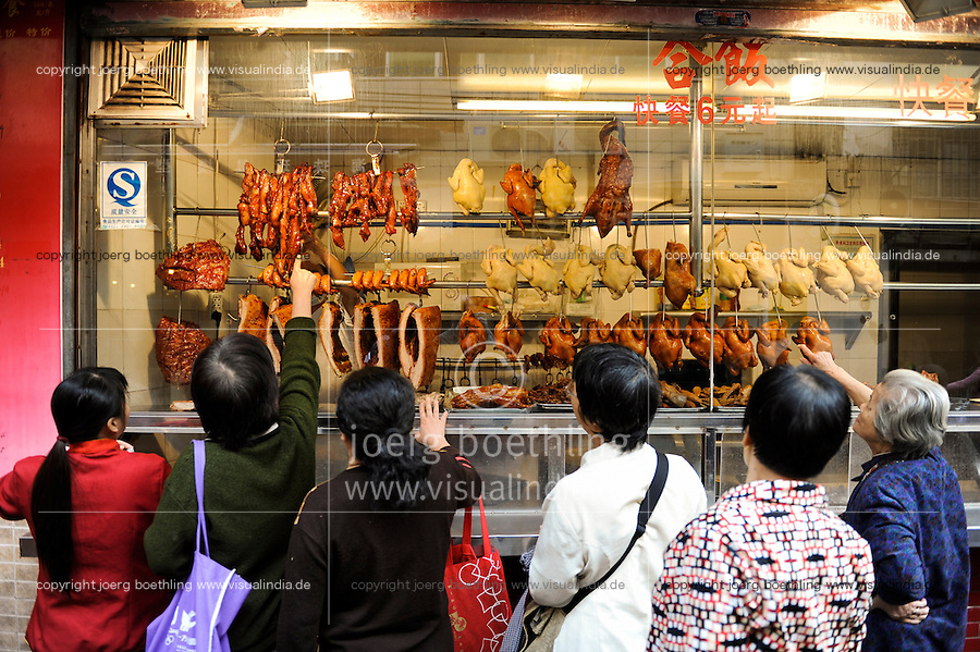 CHINA , Provinz Guangdong , Metropole Guangzhou (Kanton) Frauen vor einer Fleisch Theke / CHINA Guangzhou, women watch meat at a butchery, pork duck chicken