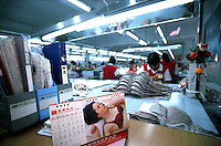 Underwear garment workers churn out bras behind a calendar at the Meisi Underwear Factory in Nanhai, Guangdong, China. The city of Nanhai is China's underwear manufacturing center. .07-SEP-01