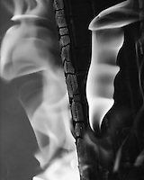Flames of fire flowing upward in hypnotic fashion.<br /> Converted here to high contrast black & white.