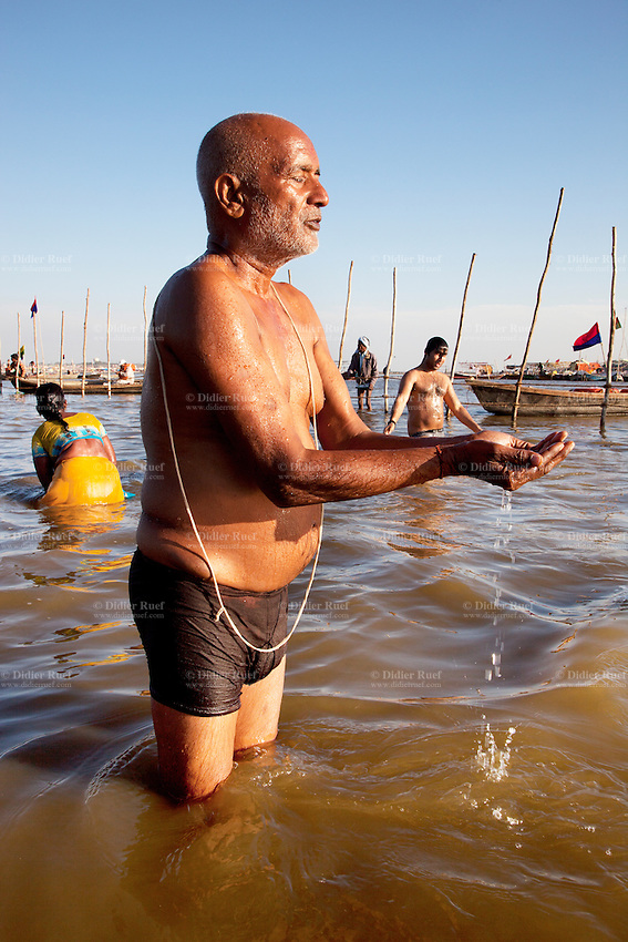 India. Uttar Pradesh state. Allahabad. Maha Kumbh Mela. An Indian Hindu devotee takes a holy dip at Sangam. The old man offers water to Mother Ganges (the river is a deity) and prays. The man wears a Janeu which is a consecrated thread worn by each and every Hindu Brahmin of India. The Kumbh Mela, believed to be the largest religious gathering is held every 12 years on the banks of the 'Sangam'- the confluence of the holy rivers Ganga, Yamuna and the mythical Saraswati. In 2013, it is estimated that nearly 80 million devotees took a bath in the water of the holy river Ganges. The belief is that bathing and taking a holy dip will wash and free one from all the past sins, get salvation and paves the way for Moksha (meaning liberation from the cycle of Life, Death and Rebirth). Bathing in the holy waters of Ganga is believed to be most auspicious at the time of Kumbh Mela, because the water is charged with positive healing effects and enhanced with electromagnetic radiations of the Sun, Moon and Jupiter. The Maha (great) Kumbh Mela, which comes after 12 Purna Kumbh Mela, or 144 years, is always held at Allahabad. Uttar Pradesh (abbreviated U.P.) is a state located in northern India. 7.02.13 © 2013 Didier Ruef
