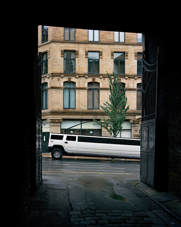 © John Angerson<br /> Bradford, West Yorkshire <br /> A stretched Hummer vehicle waits to collect a newly-married couple outside the Bradford Registry Office. It is estimated that 60% of Pakistani and Bangladeshi marriages in Bradford in 2001 involved a spouse from the subcontinent.