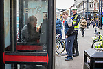 © Joel Goodman - 07973 332324 . 06/04/2017 . Manchester , UK . A paramedic tends to a man , believed to have consumed spice , in Piccadilly Gardens , as another man consumes a rolled cigarette believed to contain spice , in an adjacent telephone box . An epidemic of abuse of the drug spice by some of Manchester's homeless population , in plain sight , is causing users to experience psychosis and a zombie-like state and is daily being witnessed in the Piccadilly Gardens area of Manchester , drawing large resource from paramedic services in the city centre . Photo credit : Joel Goodman