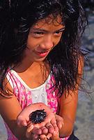 Young girl examining sea urchin