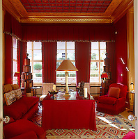 A pair of tiered bookshelves creates an unusual display in this red library