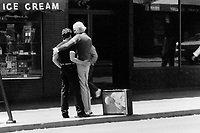 USA. State of California. San Francisco. Castro Street. Two men, both homosexuals, hold each other in the arms and hug on the street near an ice cream shop. Loving couple. A suitcase with the image of Pope John Paul II is taped on a suitcase which lies on the sidewalk. © 1981 Didier Ruef
