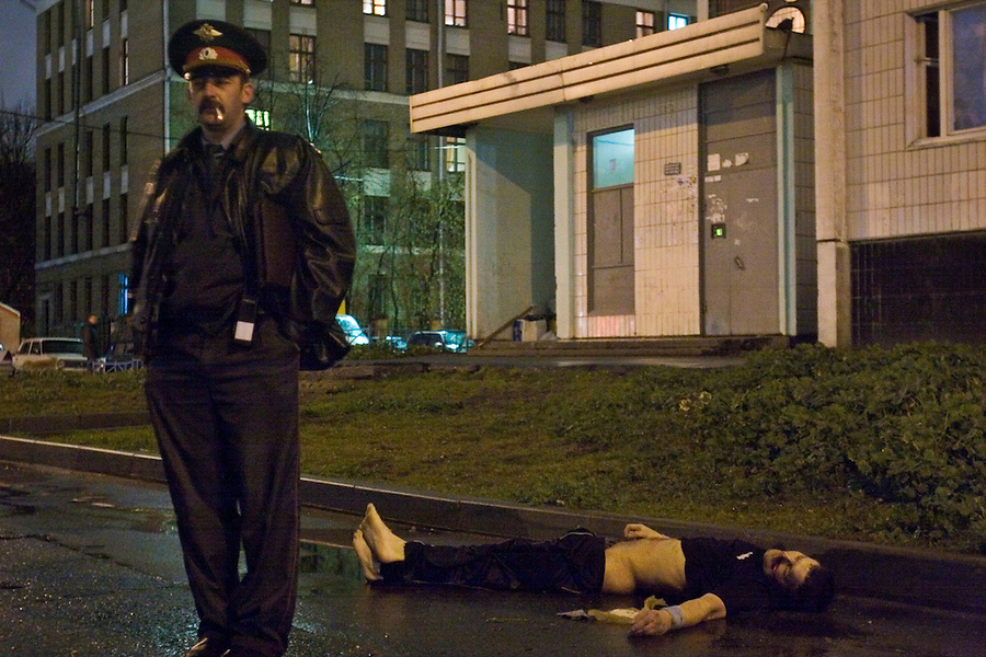 Moscow, Russia, 24/10/2005..A Russian police officer stands beside the body of a man who had been stabbed and then thrown from the balcony of a 17th floor apartment. Neighbours claimed that the apartment was used for the sale of illegal drugs.