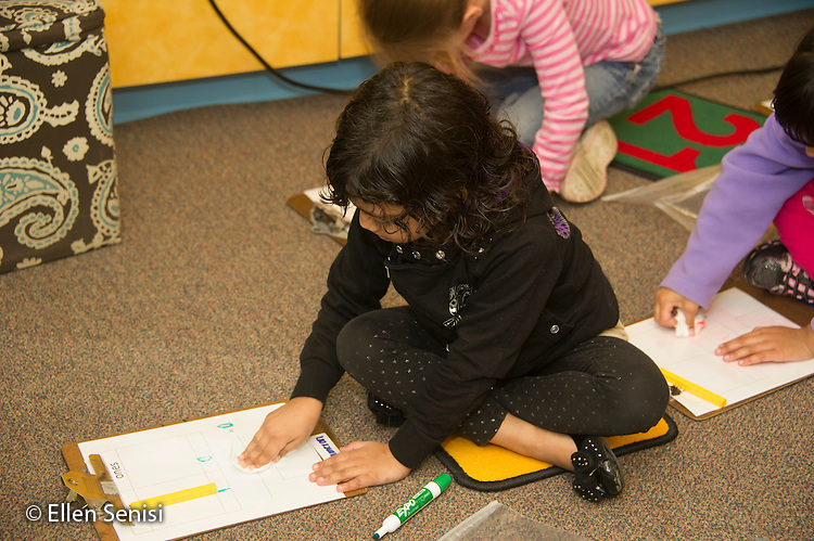 MR / Schenectady, NY. Zoller Elementary School (urban public school). Kindergarten inclusion classroom. Student (girl, 5) erases erasable worksheet during math lesson on place value. Students use math manipulatives (base ten blocks) to show tens and ones then add them up to show the total number. MR: Ram13. ID: AM-gKw. © Ellen B. Senisi.