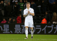 Alfie Mawson of Swansea City FC applauds the Swansea fans as he leaves the field looking dejected following the final whistle of the Premier League match between Swansea City and West Ham United at The Liberty Stadium, Swansea, Wales, UK. 26 December 2016