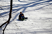 NEW YORK, NEW YORK - FEBRUARY 21: Two children slide in Central Park while is covered by snow and ice  on February 21, 2021 in New York City. The big apple waits this monday the last snowfall before a midweek warm up.  (Photo by John Smith/VIEWpress via Getty Images)