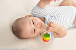 5 month old baby boy on back grasping and looking at toy with wooden disks that slide on string with moved