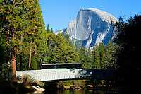 The shuttle bus on the  bridge over Merecd River with Half Dome in the background, Yosemite National Park, California.