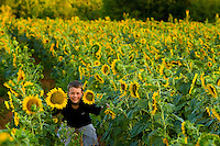 A young boy poses with in the expansive sunflower fields located within the Draper Tracts Wildlife Management Area in Brattonsville, SC. Model released.