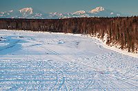 Teams run down the Yentna River with Denali in the background a few hours after leaving the Restart of the 2016 Iditarod in Willow, Alaska.  March 06, 2016.