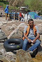 Mytilini / Lesbos / Greece 060416<br /> A refugee just landed on the island of Mytilini is resting on the rocks with a life jacket worn during the crossing between the Turkish and Greek coast. In the background a camp with tents organized by groups of volunteers.<br /> Photo Livio Senigalliesi