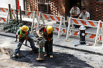 Road works on Downing Street, New York City, after digging up the street to lay new utility access.
