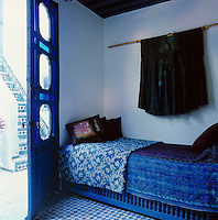 In the blue and white bedroom a day bed with patterned and plain covers stands behind the door. Above it hangs an ethnic garment as decoration