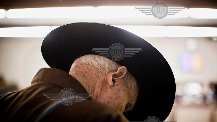 A man wearing a cowboy's ten gallon hat attends a cattle auction in Dodge City, Kansas.