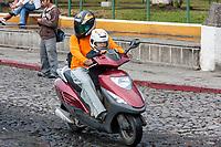 Antigua, Guatemala.  Man and Boy on Motorbike, with Helmets.