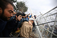 Pictured: Refugees throw stones and batter down the barbed wire gate of the fence Monday 29 February 2016<br /> Re: A crowd of migrants has burst through a barbed-wire fence on the FYRO Macedonia-Greece border using a steel pole as a battering ram.<br /> TV footage showed migrants pushing against the fence at Idomeni, ripping away barbed wire, as FYRO Macedonian police let off tear gas to force them away.<br /> A section of fence was smashed open with the battering ram. It is not clear how many migrants got through.<br /> Many of those trying to reach northern Europe are Syrian and Iraqi refugees.<br /> About 6,500 people are stuck on the Greek side of the border, as FYRO Macedonia is letting very few in. Many have been camping in squalid conditions for a week or more, with little food or medical help.