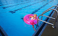 A young girl with a pink flotation device tube pulls herself from the pool as the last child to leave the water on the final day of summer swimming at an outdoor community pool.