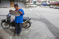 Middle-aged Man Reading Malaysian Newspaper, Ipoh, Malaysia.
