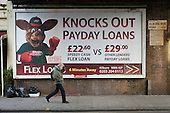 A pedestrian walks past an advertisement for loans at an interest rate of 1373% APR in Kilburn, London.