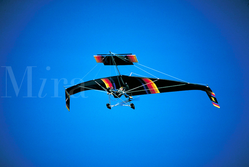 Close-up of an ultralight aircraft in a clear blue sky above Cedar Valley Airport. sports, aviation Connotations Freedom, daring. Utah, Cedar Valley.