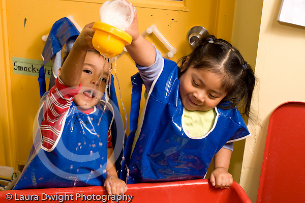 Education Preschool 3-4 year olds water table a boy and a girl playing together horizontal