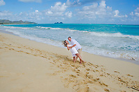 A husband playfully dipping his laughing wife on the sunny shore of Waimanalo Beach, O'ahu.