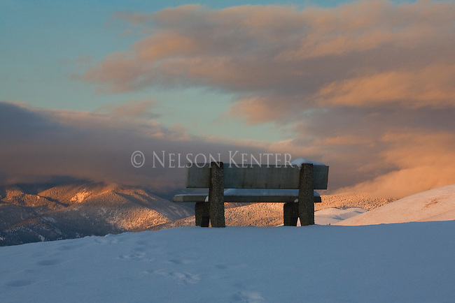 A winter evening scene of a park bench on a hill overlooking the Missoula valley in western Montana