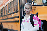 USA, New York State, New York City, Portrait of smiling girl (10-11), school bus in background