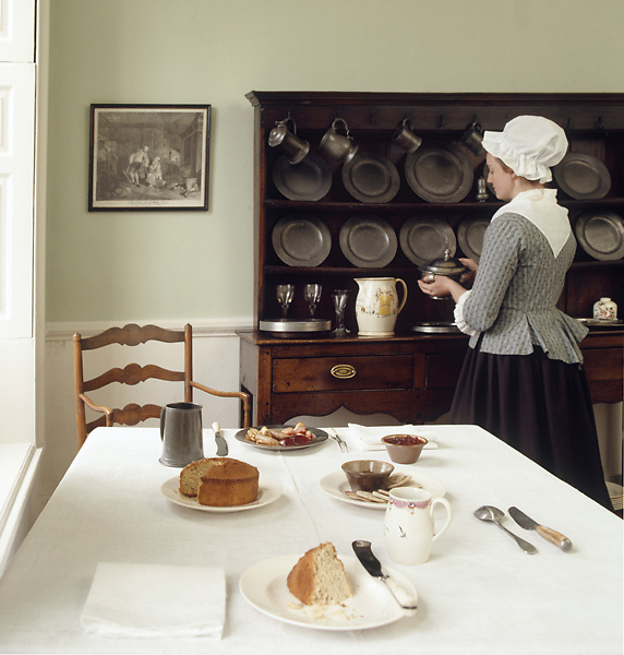 The Common Parlour at Wordsworth House, with the table laid for tea. A maid stands at the dresser, dressed as she would have been in the 1770s when this was William Wordsworth's childhood home.M.R.