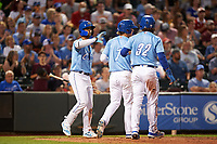 Omaha Storm Chasers Bobby Witt Jr. (7) and Nick Pratto (32) are congratulated by MJ Melendez (2) after scoring runs during a game against the Iowa Cubs on August 14, 2021 at Werner Park in Omaha, Nebraska. Omaha defeated Iowa 6-2. (Zachary Lucy/Four Seam Images)