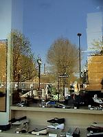 The reflected image of a Parisian urban landscape, with a metro station, some trees and the Eiffel tower on the background, on a shoes' shop window. There is a woman who is walking on the distance (Paris, 2007).<br /> <br /> L'immagine riflessa di un paesaggio urbano Parigino, con una stazione della metro, alcuni alberi e la torre Eiffel sullo sfondo, sulla vetrina di un negozio di scarpe. C'è una donna che cammina in lontananza (Parigi, 2007)