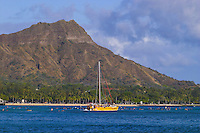 Vacationing tourists on an afternoon cruise sail by scenic Diamond Head Crater, Oahu.
