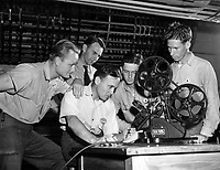 Students in class 4 (movies) Naval School of Photography editing their films, suing the moviola edition machines.  Instructor H.T. Hung Jr., PhoM 1/c.  H.T. Hunt Jr., explaining the use of the Moviola film editing viewer.