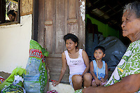 Philippines. Province Eastern Samar. Hernani. On orphanage's threshold (Nordic Harvest Bible Community Child Care Center), which served as an emergency evacuation center during Typhoon Haiyan and now converted into a place of temporary accommodation, Juvac Calvadores (center) and her son Elmerson (center right), 5 years old. Juvac Calvadores has lost her younger son Winston, 5 months old, during Typhoon Haiyan. 95 % of the town was destroyed by typhoon Haiyan's winds and storm surge. Typhoon Haiyan, known as Typhoon Yolanda in the Philippines, was an exceptionally powerful tropical cyclone that devastated the Philippines. Haiyan is also the strongest storm recorded at landfall in terms of wind speed. Typhoon Haiyan's casualties and destructions occured during a powerful storm surge, an offshore rise of water associated with a low pressure weather system. Storm surges are caused primarily by high winds pushing on the ocean's surface. The wind causes the water to pile up higher than the ordinary sea level. 25.11.13 © 2013 Didier Ruef